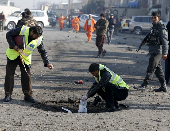 Afghan security forces investigate at the site of a suicide bomb attack in Kabul