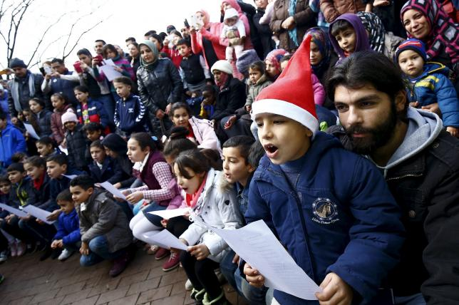 "Migrants sing the traditional German christmas carol ""Oh christams tree"" during a Christmas gathering, organized by local relief organization ""Die Johanniter"", with christmas presents for the children at the refugee camp in Hanau, Germany"