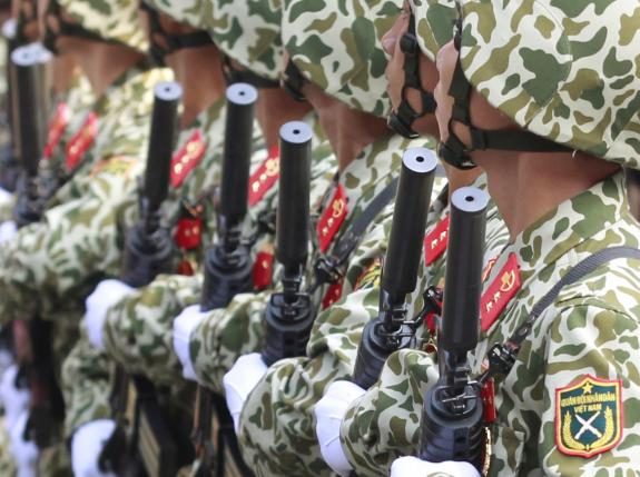 Soldiers hold U.S.-designed, Israeli-made M4 rifles while marching during a celebration to mark Reunification Day in Ho Chi Minh city
