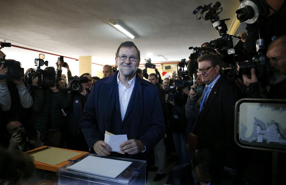 Spain's Prime Minister and Popular Party (PP) candidate Mariano Rajoy holds his ballot before casting his vote in Spain's general election in Madrid