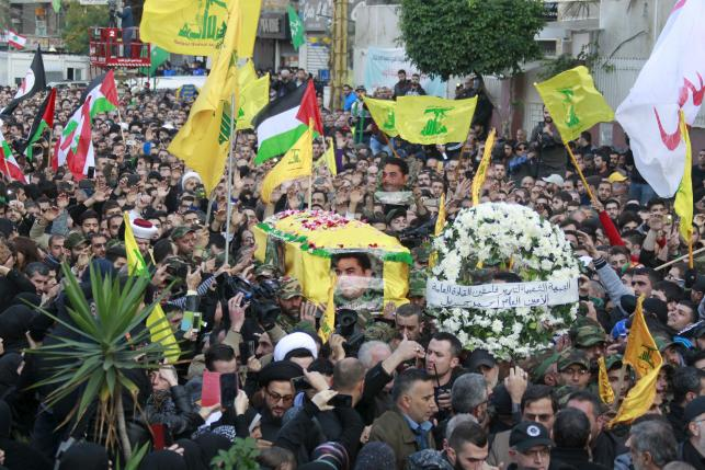 Hezbollah members carry the coffin of Hezbollah militant leader Qantar, as supporters wave Lebanese, Palestinian and Hezbollah flags, during his funeral in Beirut's southern suburbs