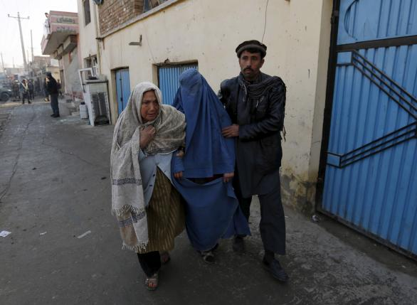 An injured Afghan woman is assisted by her relatives after she was wounded by a suicide attack Kabul