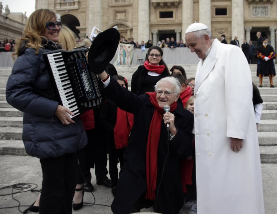 Italian singer Teddy Reno kneels as he sings next to Pope Francis after the weekly audience in Saint Peter's square at the Vatican