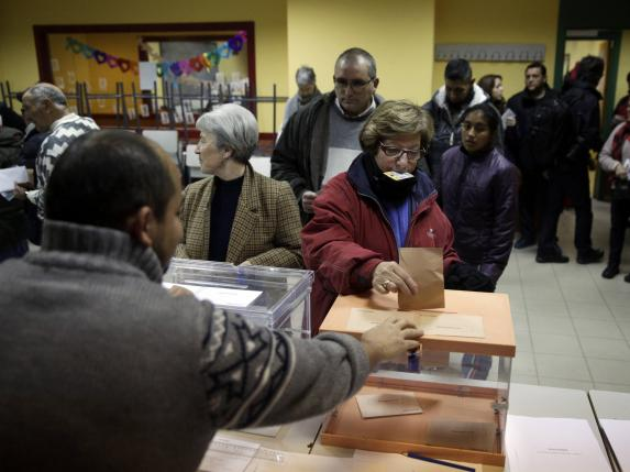A woman holds her identity card in her mouth while voting in Spain's general election in Madrid