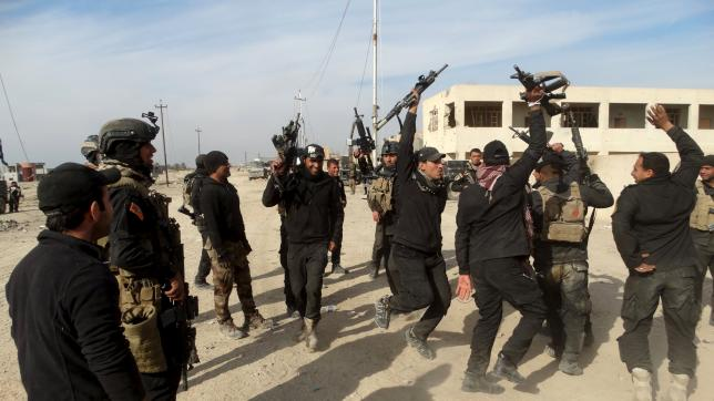 Iraqi security forces chant slogans in the city of Ramadi