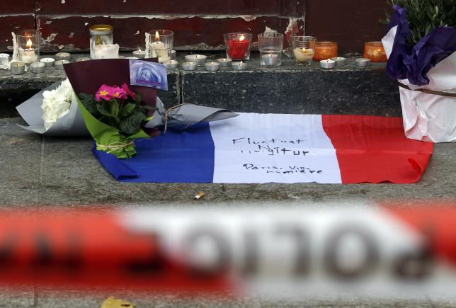 Flowers and candles are seen placed outside the Le Carillon restaurant the morning after a series of deadly attacks in Paris