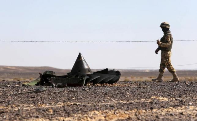 An Egyptian army soldier stands guard near debris from a Russian airliner which crashed at the Hassana area in Arish city
