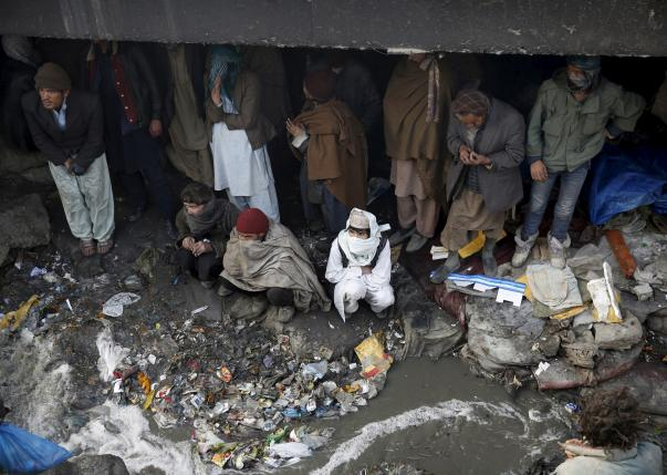 People shelter under the Pul-e Sokhta bridge in western Kabul, during a police round up of suspected drug addicts