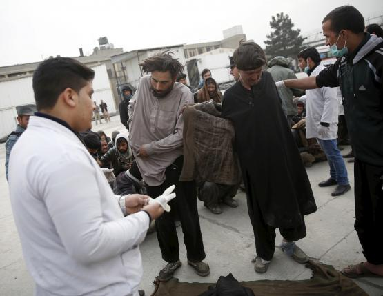 Health workers help to undress people at a newly-opened treatment centre at Camp Phoenix, after a police round up of suspected drug addicts in Kabul, Afghanistan