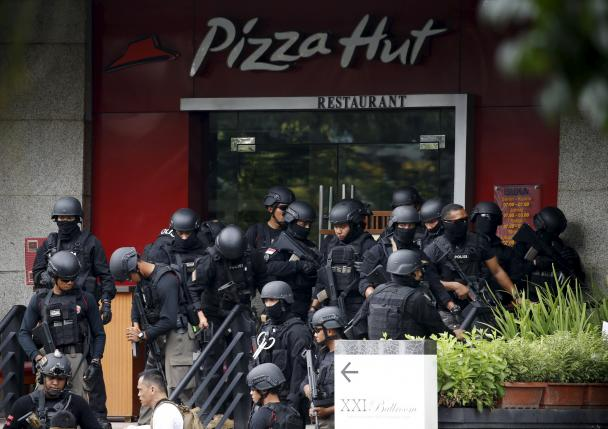 Police gather outside a restaurant near the scene of an attack in central Jakarta