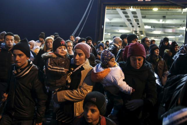 Refugees and migrants arrive aboard the passenger ferry Nissos Rodos at the port of Piraeus, near Athens
