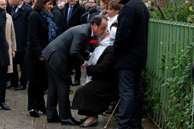French President Hollande and Paris Mayor Hidalgo greet the mother of Ahmed Merabet, the policeman who was killed during the last year's January attack, during a ceremony at the site in Paris