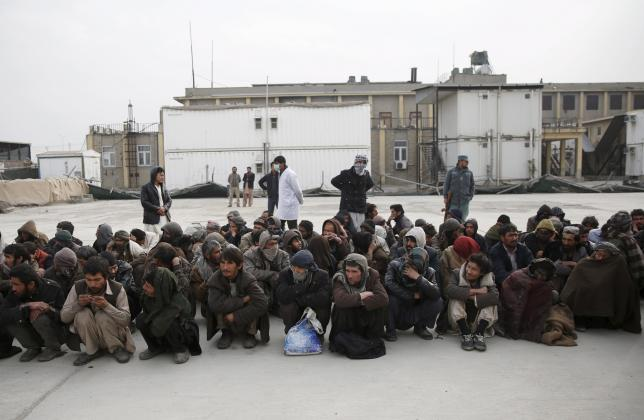 People sit in lines at a newly-opened treatment centre at Camp Phoenix, after a police round up of suspected drug addicts in Kabul, Afghanistan