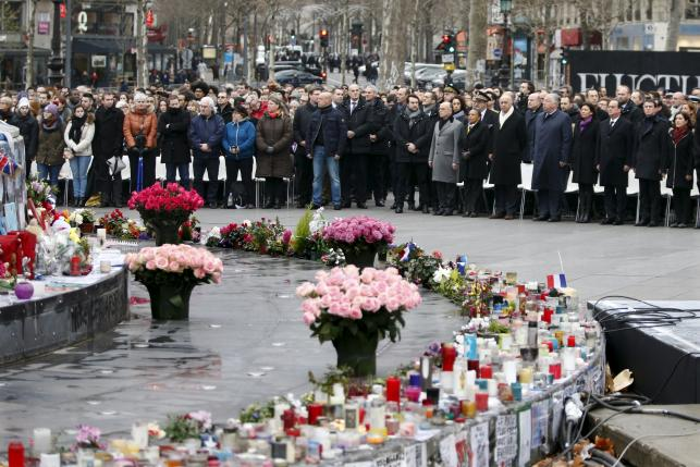 People attend a ceremony at Place de la Republique square to pay tribute to the victims of last year's shooting at the French satirical newspaper Charlie Hebdo, in Paris
