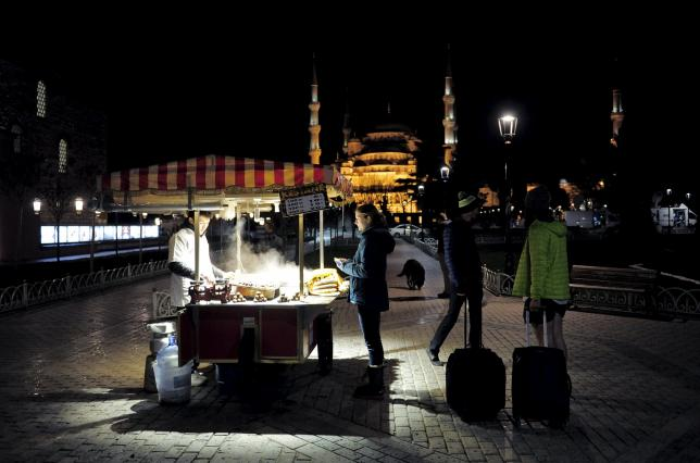 Foreign tourists stand next to a street vendor at Sultanahmet square in Istanbul, Turkey