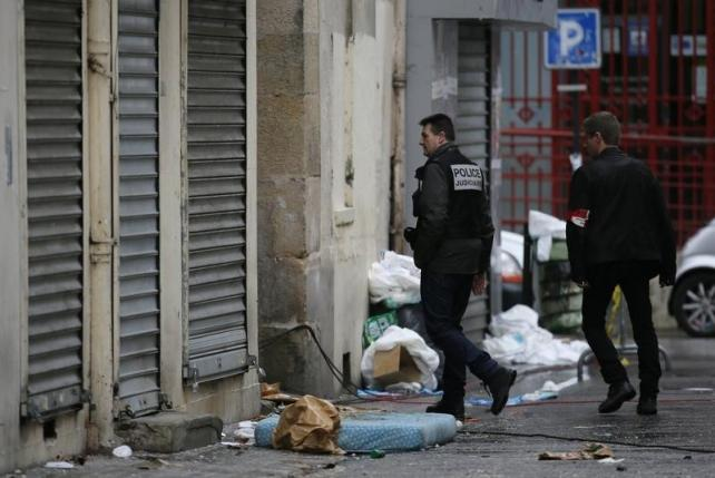 A member of French judicial police and a French plainclothes policeman walk outside a building in Saint-Denis, near Paris