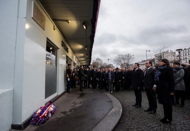 French President Hollande, French Prime Minister Valls and Mayor of Paris Hidalgo stand at attention after unveiling a commemorative plaque outside the Hypercacher kosher supermarket in Paris