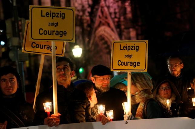 """Participants hold candles and posters reading """"Lepizig shows courage"""" during a protest against LEGIDA, the Leipzig arm of the anti-Islam movement PEGIDA, in front of St. Nicholas Church in Leipzig"""