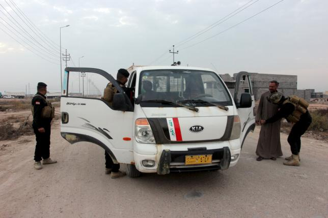 Iraqi security forces search vehicles in Basra province