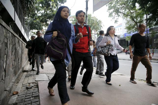 Indonesian workers run as they are evacuated from their office at Thamrin business district in Jakarta