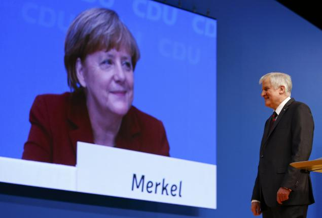 German Chancellor and leader of the CDU Merkel is seen on a video screen as Bavarian Prime Minister and head of the CSU Seehofer makes a speech at the CDU party congress in Karlsruhe, file