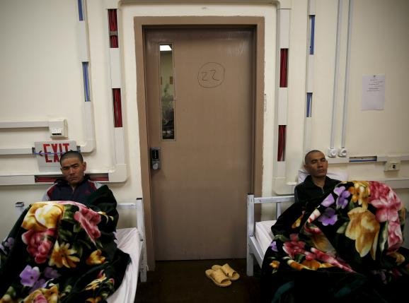 Drug addicts sit on their beds at a newly-opened treatment centre at Camp Phoenix, in Kabul, Afghanistan