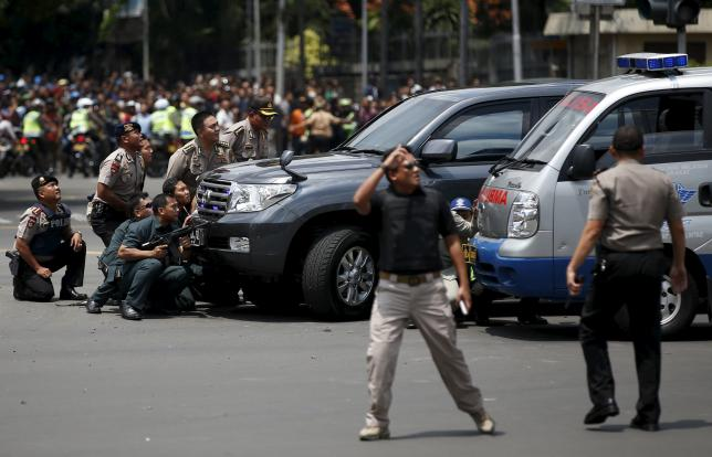 Police officers react near the site of a blast in Jakarta