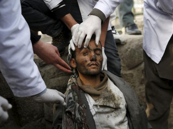 Doctors check on a man during a police round up of suspected drug addicts, in Kabul, Afghanistan