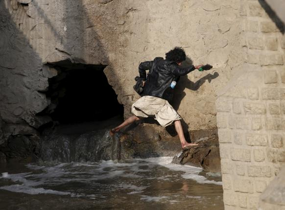 A man runs away during a police round up of suspected drug addicts in Kabul, Afghanistan