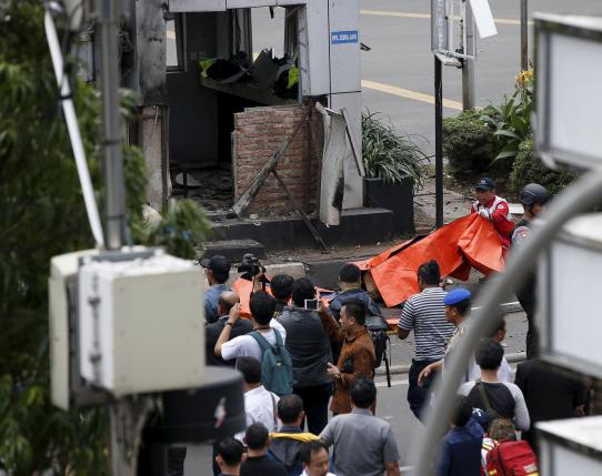Police and medics are seen near bodies at the scene of an explosion next to a police box in central Jakarta