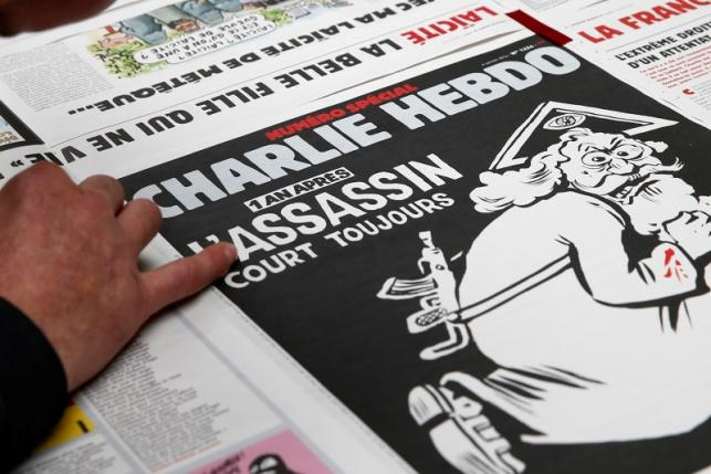 An employee of a printing house checks a copy of the latest edition of French weekly newspaper Charlie Hebdo near Paris