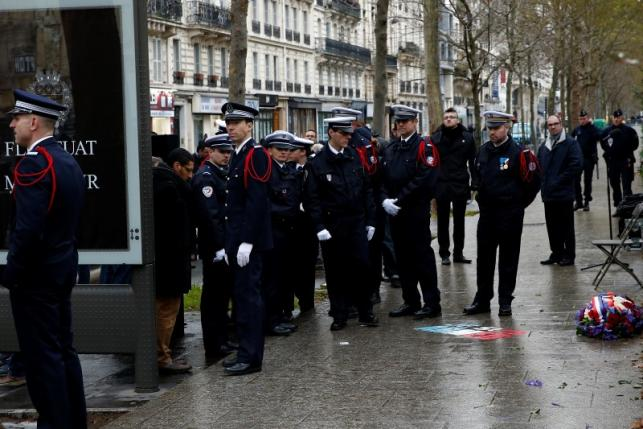 French police react after a ceremony to unveil a commemorative plaque at the site where policeman Ahmed Merabet was killed during the last year's January attack in Paris