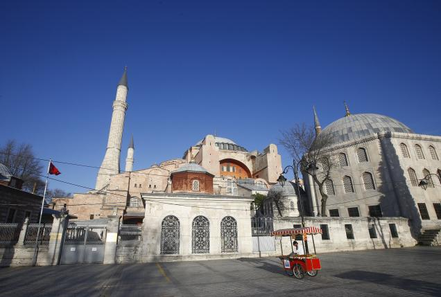 A food vendor stands in a deserted square in front of the New Mosque following an explosion in Istanbul