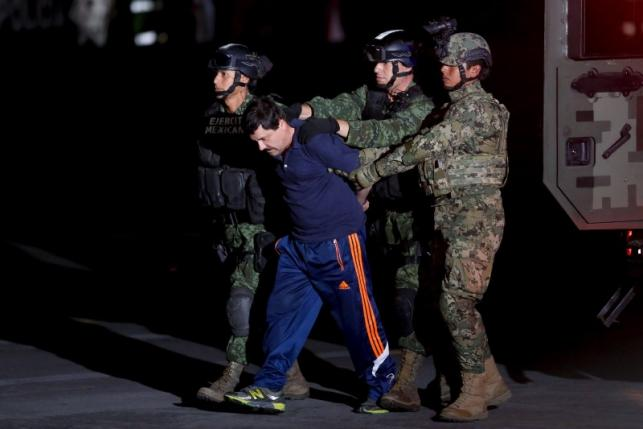 """Drug lord Joaquin """"El Chapo"""" Guzman is escorted by soldiers during a presentation in Mexico City"""