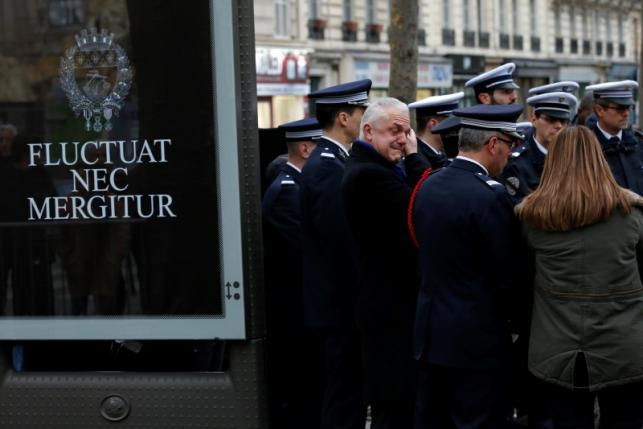 French police and officials react during a ceremony to unveil a commemorative plaque at the site where policeman Ahmed Merabet was killed during the last year's January attack in Paris