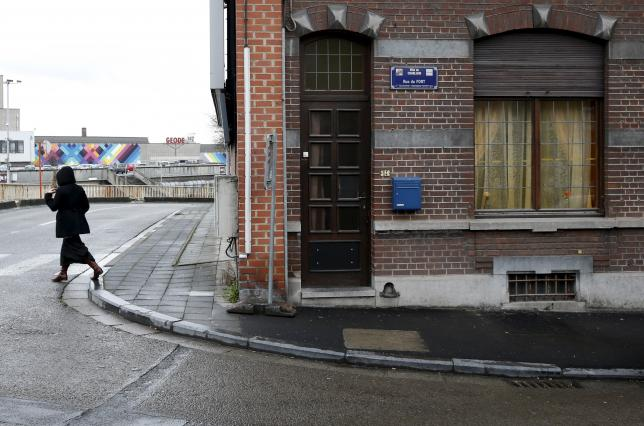 """A woman walks along a street called """"Rue du Fort"""" in Charleroi"""