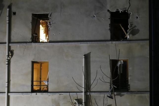 A view shows impacts around windows on the facade of the apartment raided by French Police special forces earlier in Saint-Denis, near Paris