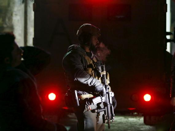 A foreign security personnel stands guard at the site of an explosion in Kabul, Afghanistan
