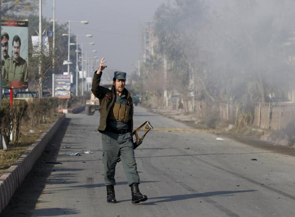 An Afghan policeman reacts as smoke billows during an attack near the Pakistani consulate in Jalalabad