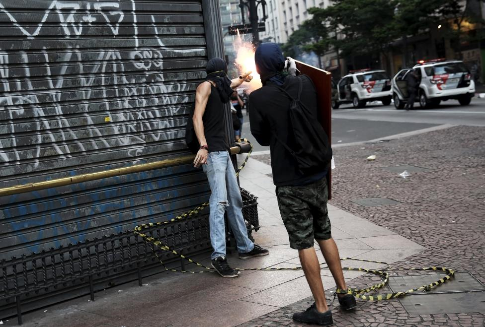 Demonstrator sets off a flare bomb against Riot police during a protest against fare hikes for city buses in Sao Paulo