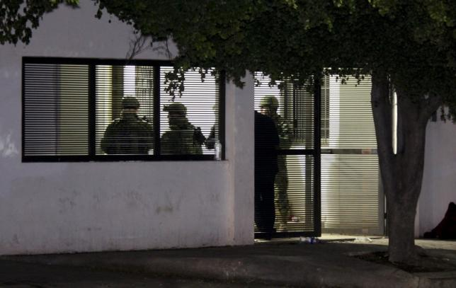 """Soldiers stand inside a safe house where five people were shot dead during an operation to recapture the world's top drug lord Joaquin """"El Chapo"""" Guzman in Los Mochis"""