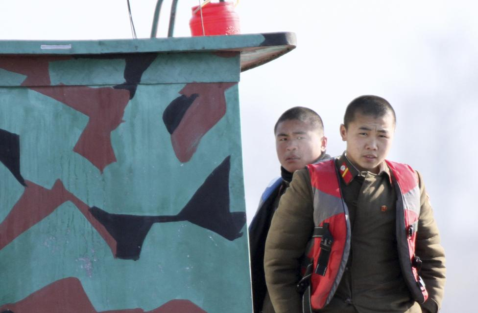 North Korean soldiers look out from a patrol boat on the Yalu River, near the North Korean town of Sinuiju