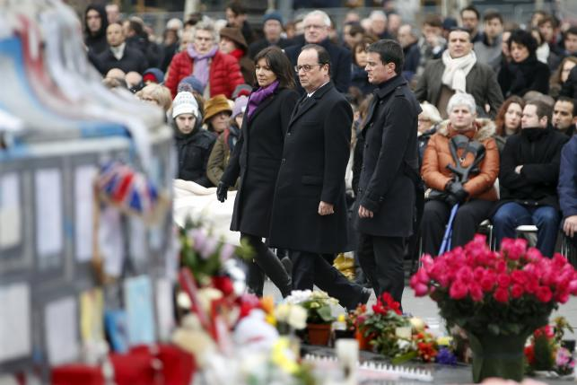 French President Francois Hollande, Prime Minister Manuel Valls and Paris Mayor Anne Hidalgo attend a ceremony at Place de la Republique square to pay tribute to the victims of last year's shooting at the French satirical newspaper Charlie Hebdo, in Paris