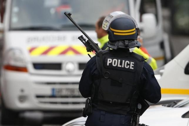 An armed French policeman secures the scene at the raid zone in Saint-Denis o catch fugitives from Friday night's deadly attacks in the French capital