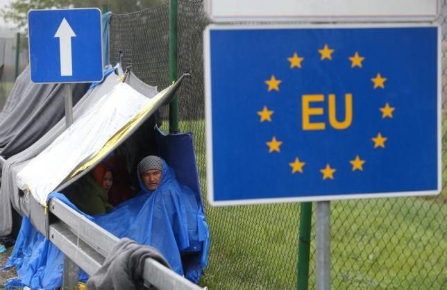An EU sign is seen as migrants wait in the no man's land to cross the border to Slovenia from Trnovec