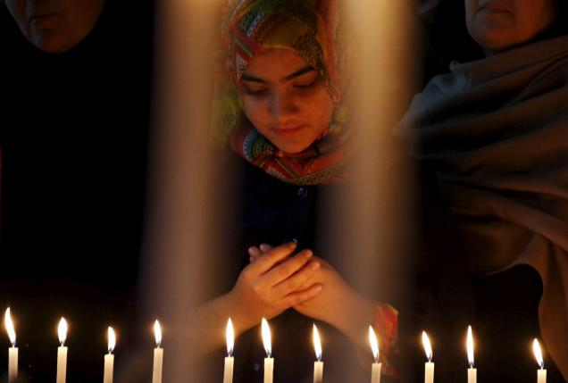 A girl prays for the victims of a militant attack on the Bacha Khan University, during a candle light vigil in Peshawar, Pakistan