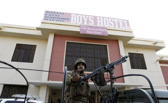 Soldier stands guard at the entrance to a dormitory where a militant attack took place, in Bacha Khan University in Charsadda