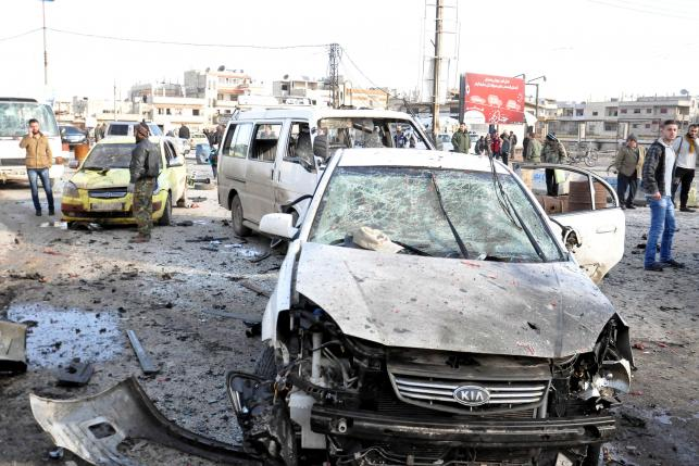 Syrian army soldiers and civilians inspect the site of a double bomb attack in the government-controlled city of Homs