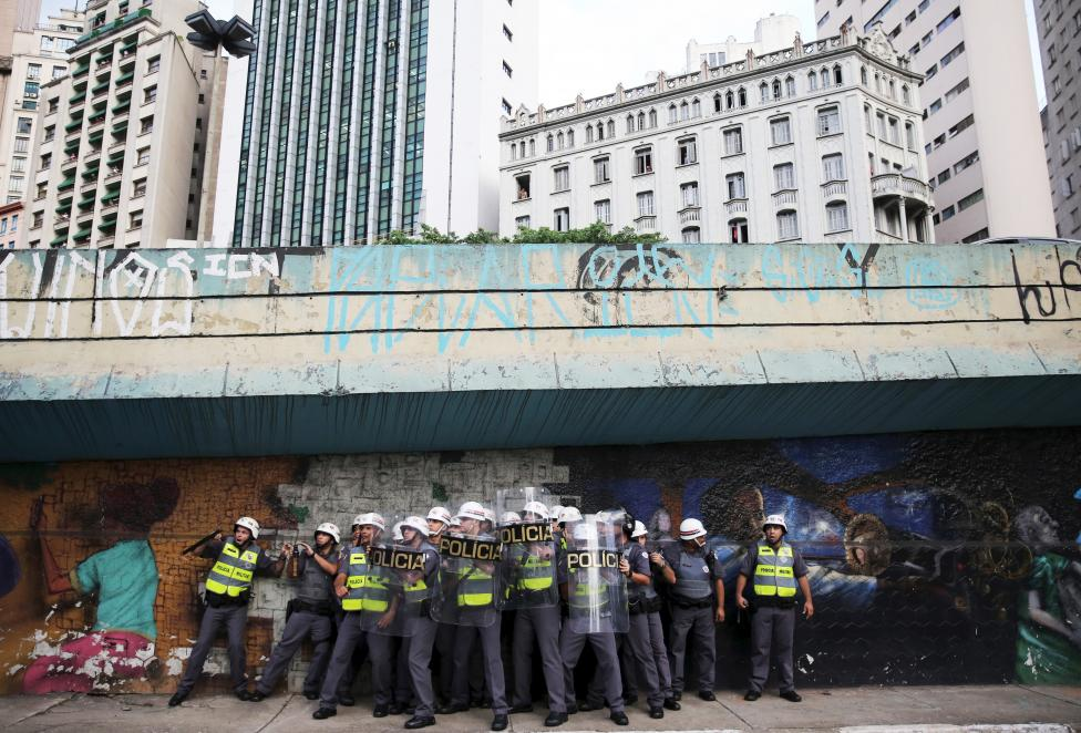 Riot police protect themselves behind shields as object are thrown at them by demonstrators during a protest against fare hikes for city buses in Sao Paulo
