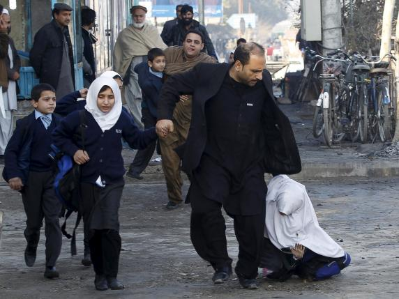 A school girl falls as she and others run after a blast near the Pakistani consulate in Jalalabad